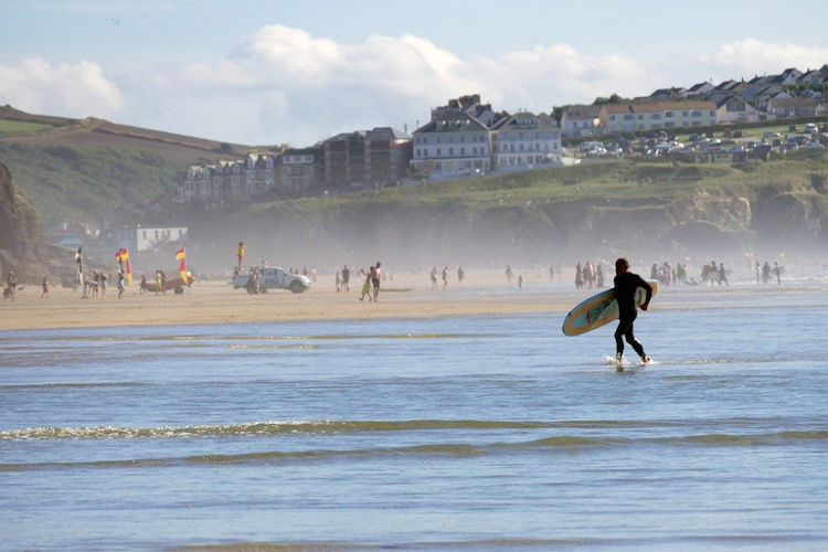 A person in a wetsuit with a surfboard running across the UK coast